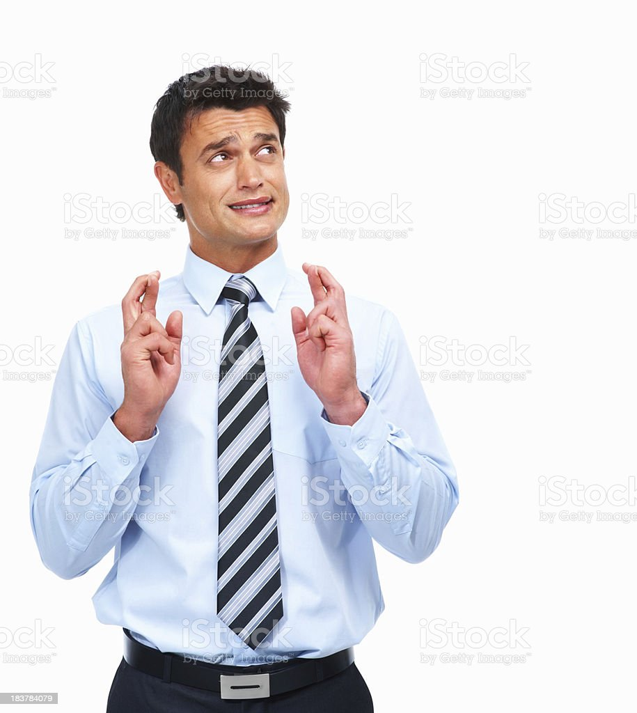 Hopeful businessman with his fingers crossed royalty-free stock photo