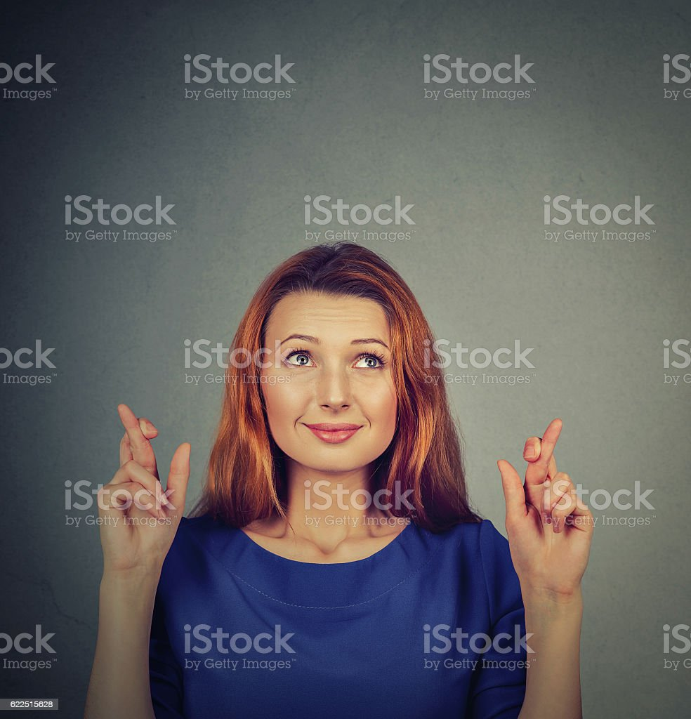 hopeful woman crossing her fingers hoping stock photo