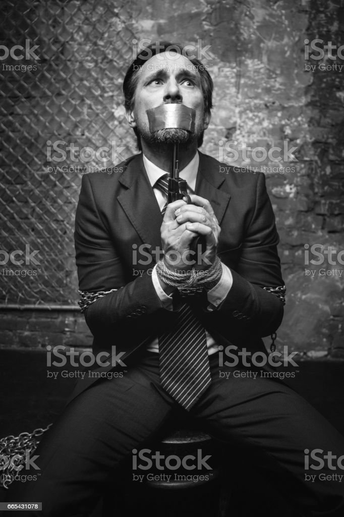 Hopeless kidnapped businessman threatening killing himself stock photo