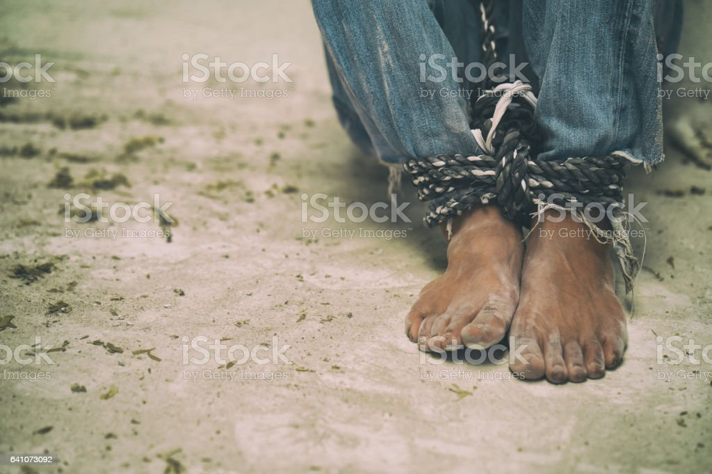 hopeless man feet tied together with rope stock photo