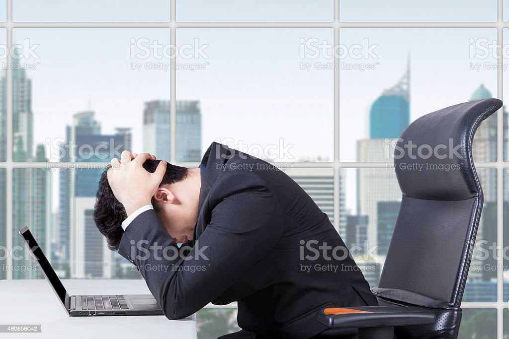 Hopeless worker working with laptop in office stock photo
