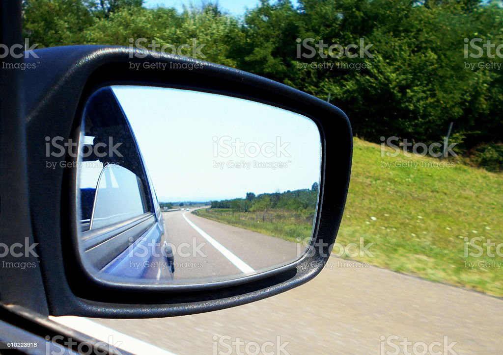 Horizon over highway in a rearview mirror stock photo