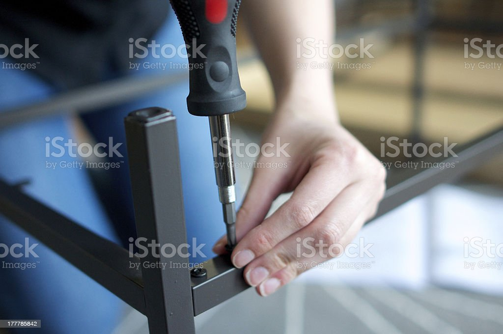 Horizontal close up of hands screwing together furniture pieces royalty-free stock photo