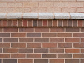 Horizontal image of a brick wall with decorative ledge.
