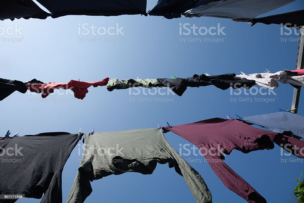 horizontal low view of shirts hanging in clothesline stock photo