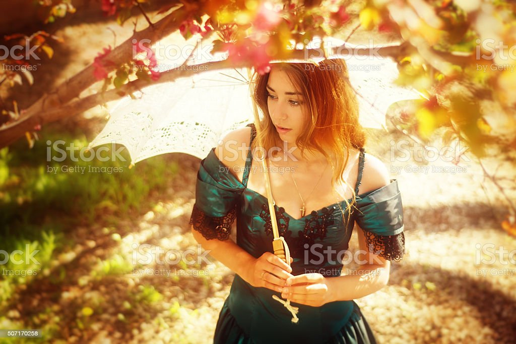 Horizontal overhead view of girl in ballgown with parasol. stock photo