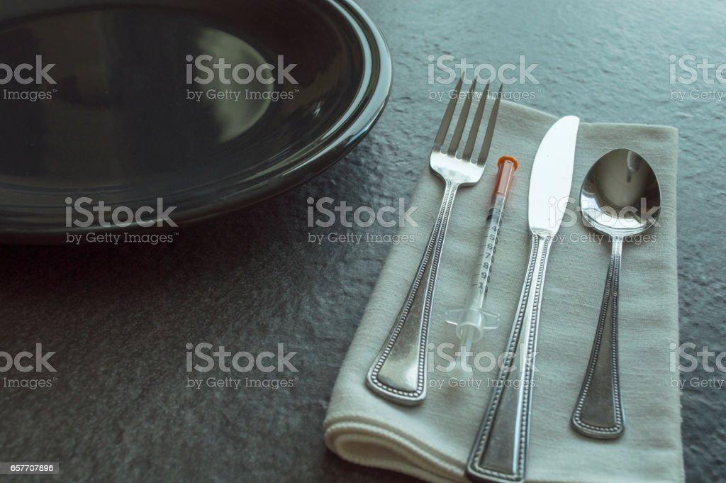 Horizontal photograph of tableware,  and diabetic syringe. stock photo