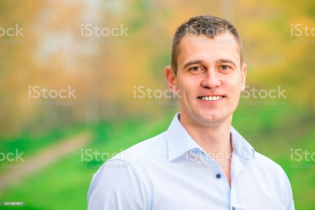 Horizontal portrait of a handsome young man on nature background stock photo