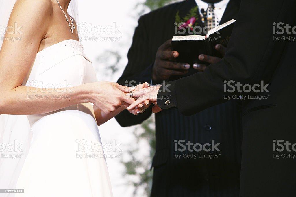 Horizontal Portrait of Bride Placing Ring on Groom stock photo