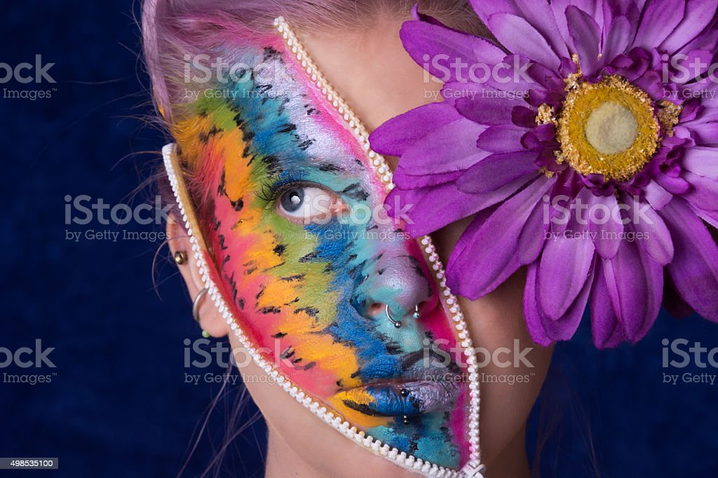 Horizontal studio shot of woman with zipper face and flower. stock photo