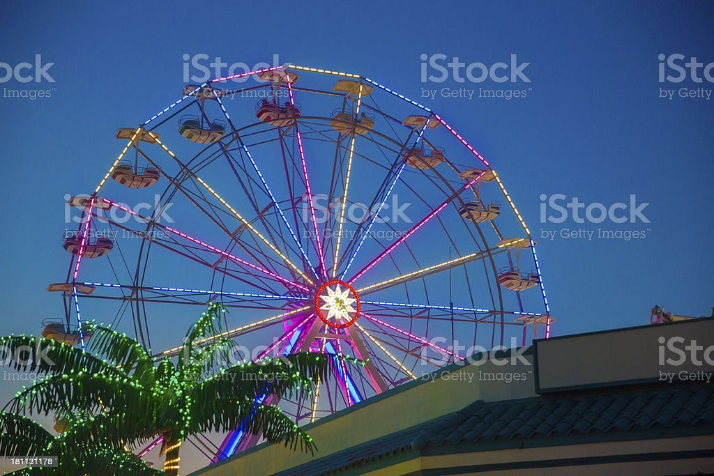 Horizontal view of a ferris wheel against a blue sky royalty-free stock photo