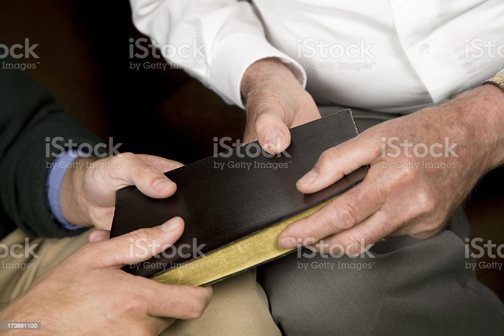 Horizontal View of Two men holding a Black Leather Bible royalty-free stock photo