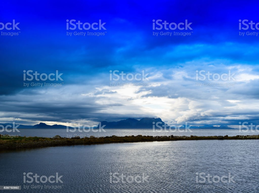 Horizontal vivid Norway fjord ocean bay with dramatic clouds bac stock photo