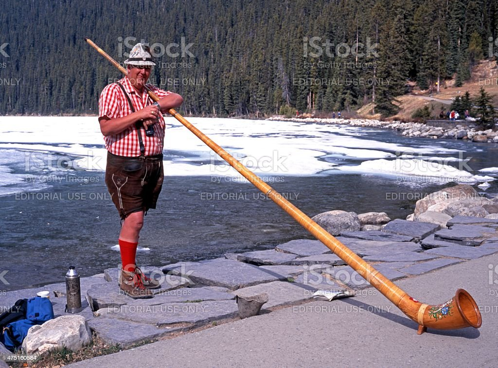 Horn blower at the edge of Lake Louise, Canada. stock photo