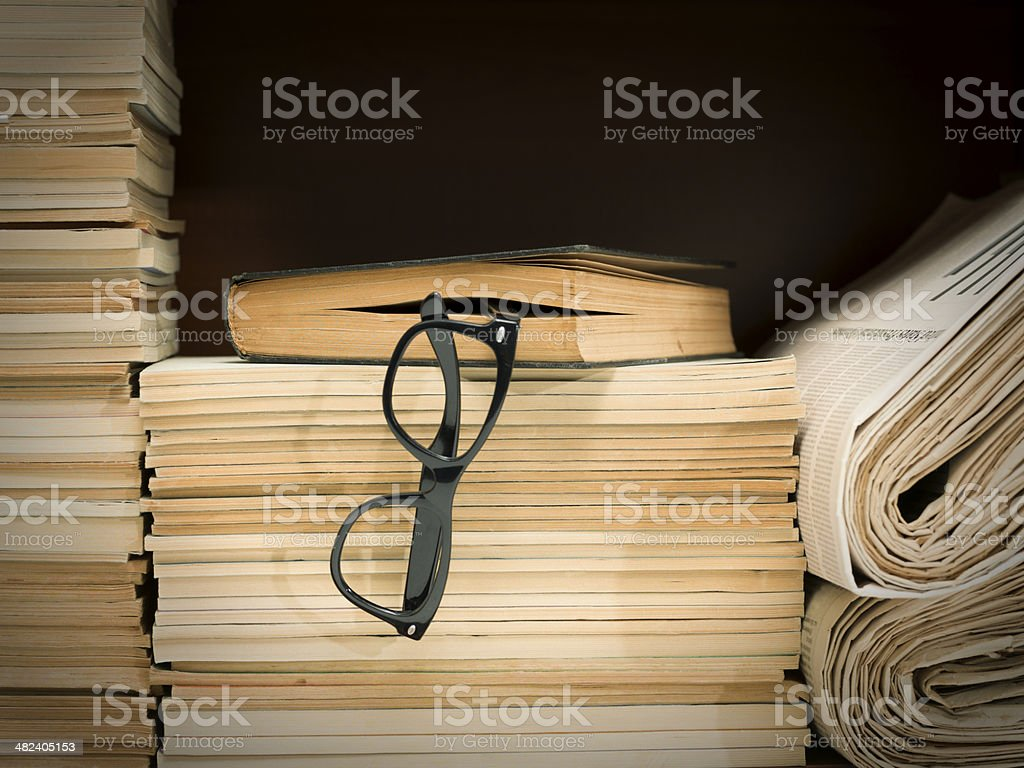 Horn rimmed glasses on large amount of book and newspapers stock photo