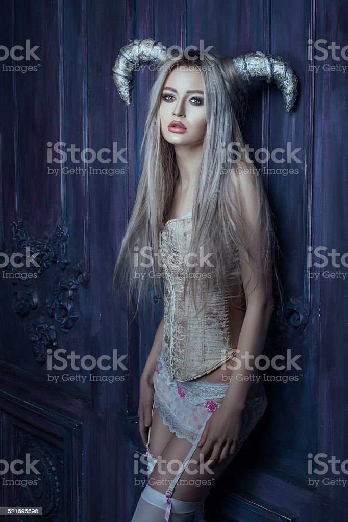 Horned woman in the room. stock photo