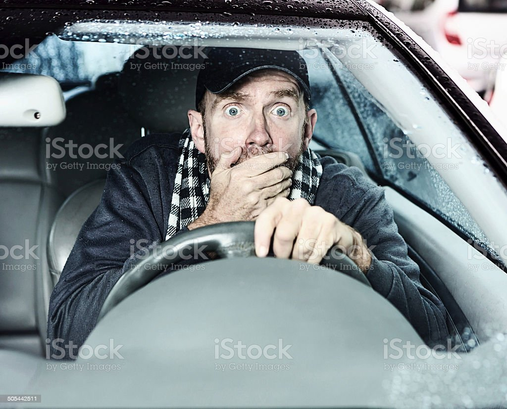 Horrified male driver, hand over mouth and eyes wide stock photo