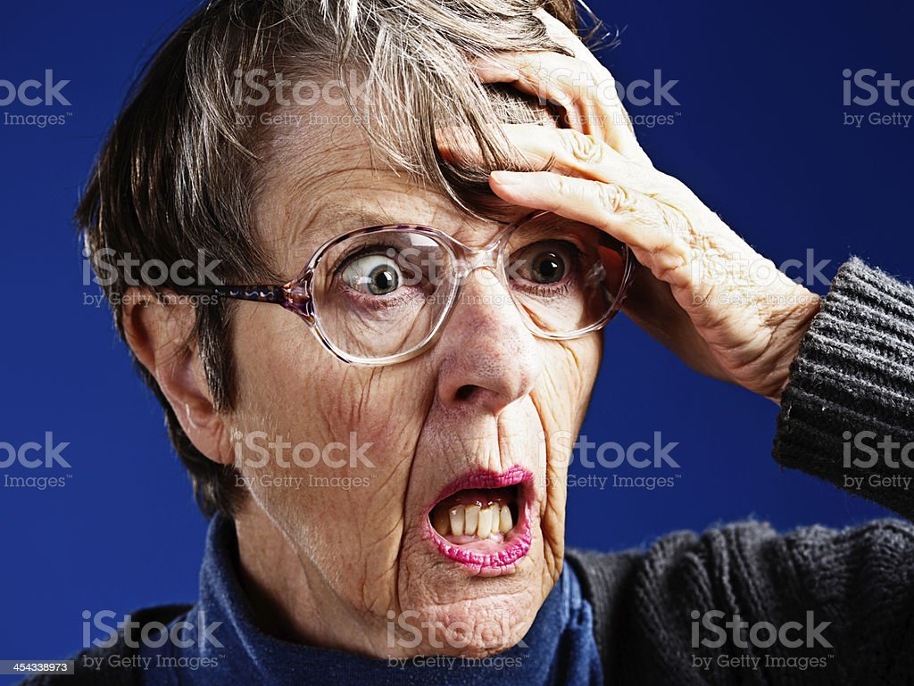 Horrified old woman clutches her head, gasping royalty-free stock photo