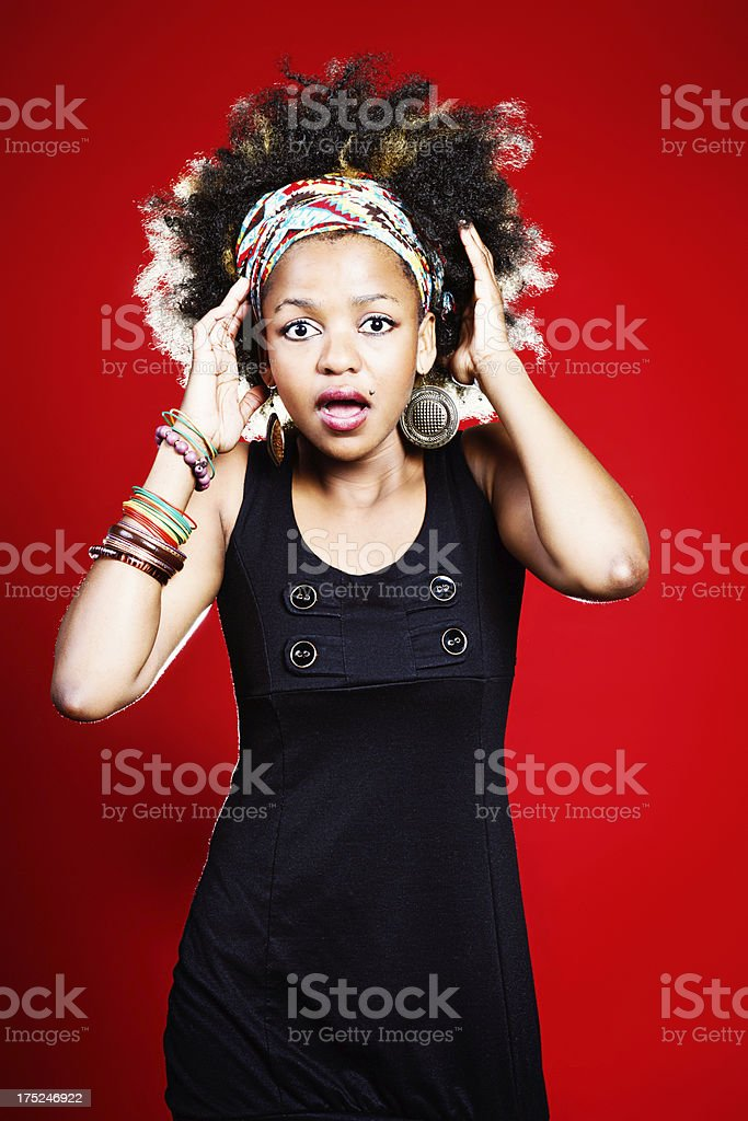 Horrified young beauty, hands to her afro-styled hair, gasps royalty-free stock photo