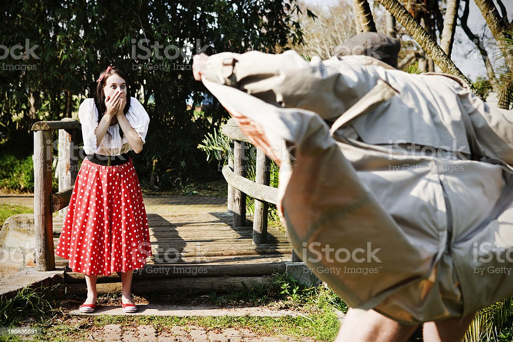 Horrified young girl confronts a flasher in the park stock photo