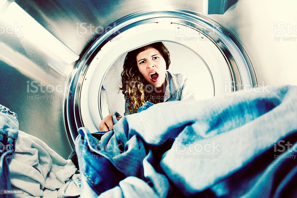 Horrified young woman grimaces at laundry in clothes drier stock photo