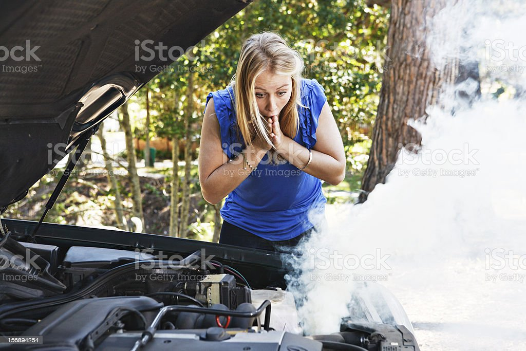 Horrified young woman, hands to mouth, eyes smoking car engine royalty-free stock photo
