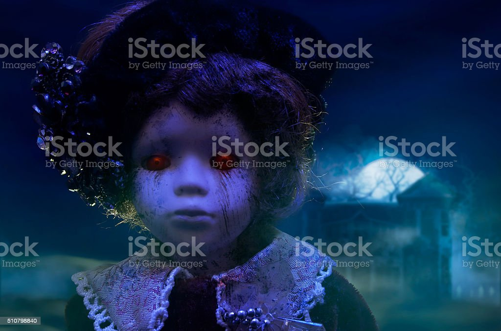 Horror doll with haunted house. stock photo