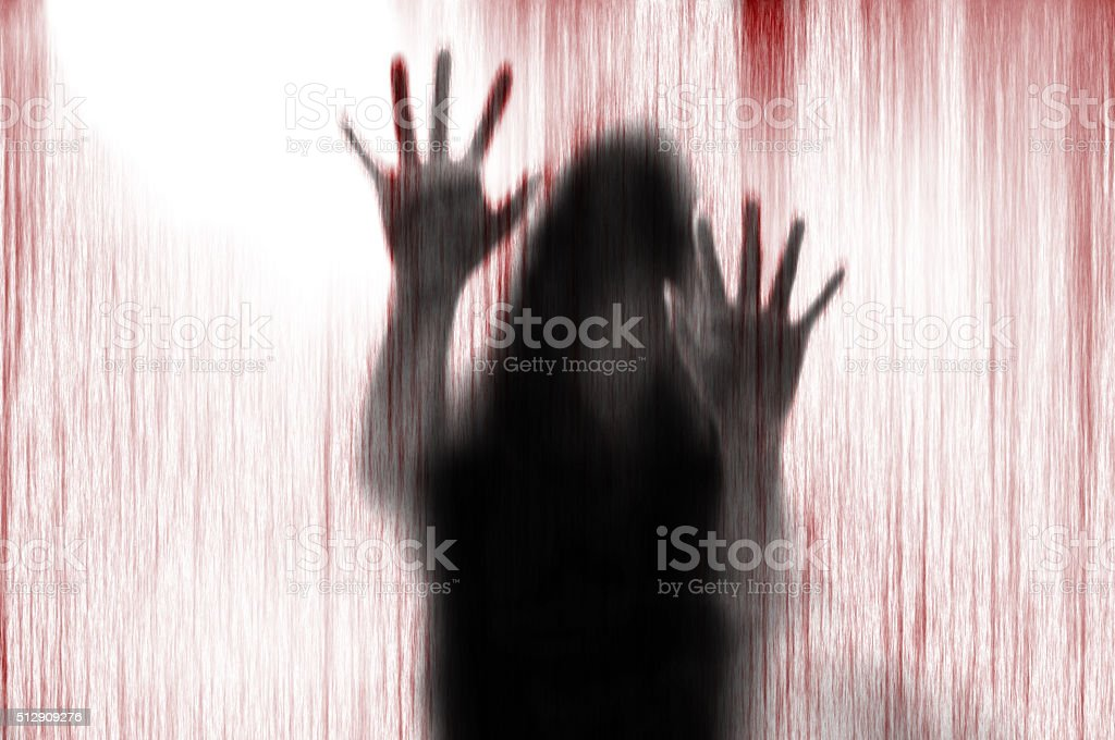 Horror woman behind the matte glass blood stain. stock photo