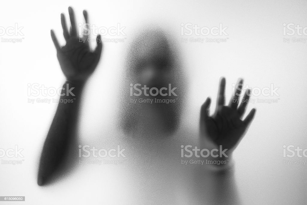 Horror woman behind the matte glass stock photo