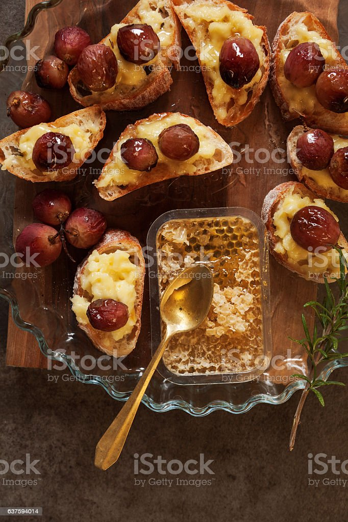 hors doeuvres with baked camembert, grapes and honey on grey stock photo