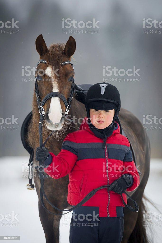 Horse and boy - riding horseback in winter stock photo