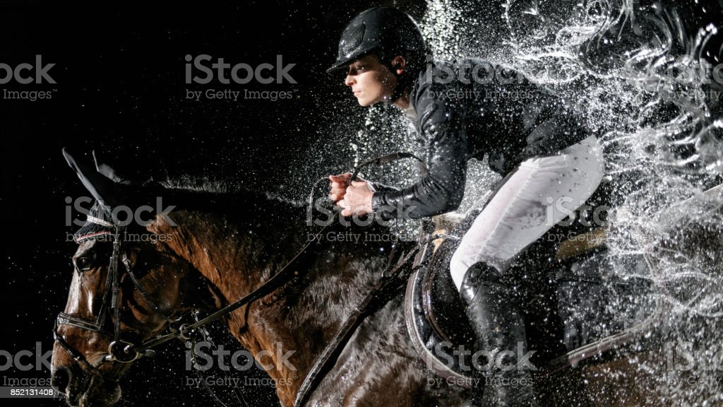 Horse and his rider jumping through water curtain stock photo