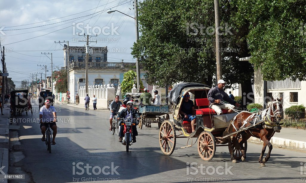 horse drawn taxi shares road with bicycles and motorcycles stock photo