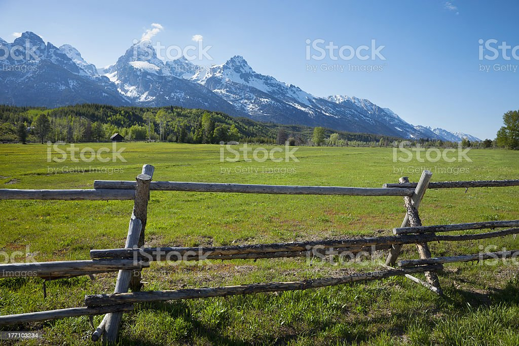 Horse ranch field and fence below Grand Tetons royalty-free stock photo