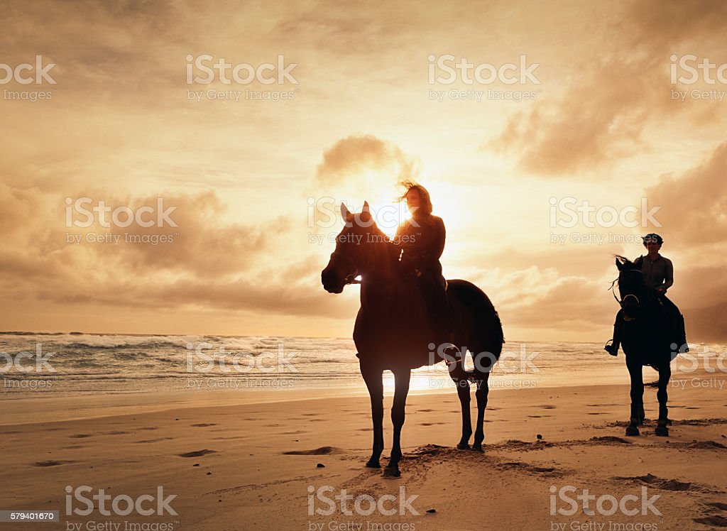 Horse riders silhouetted against setting sun on winter beach stock photo