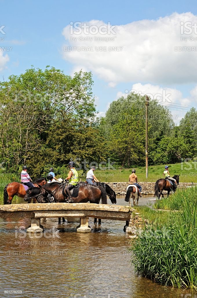 Horse riding in river, Lower Slaughter. stock photo