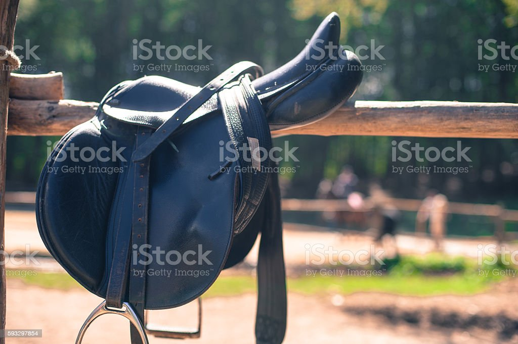 Horse saddle close up on stables fence stock photo