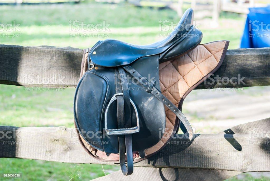 Horse saddle hanging on a wooden fence stock photo