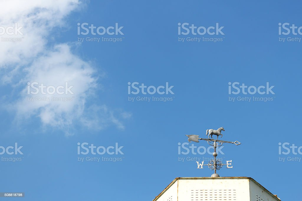 horse shaped weathercock in the cloudy blue sky stock photo