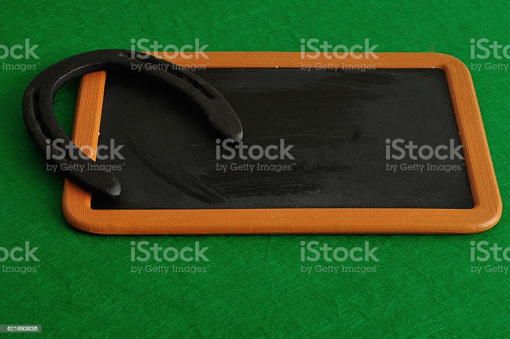 Horse shoe displayed on a black board stock photo