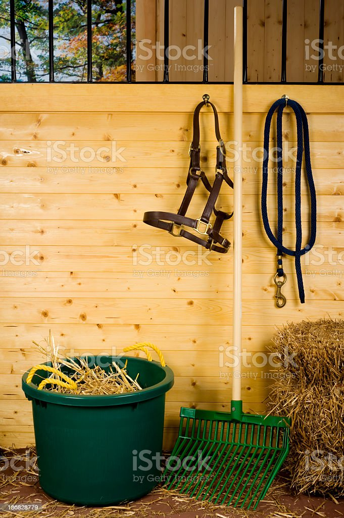 Horse stall with muck bucket and stable fork stock photo