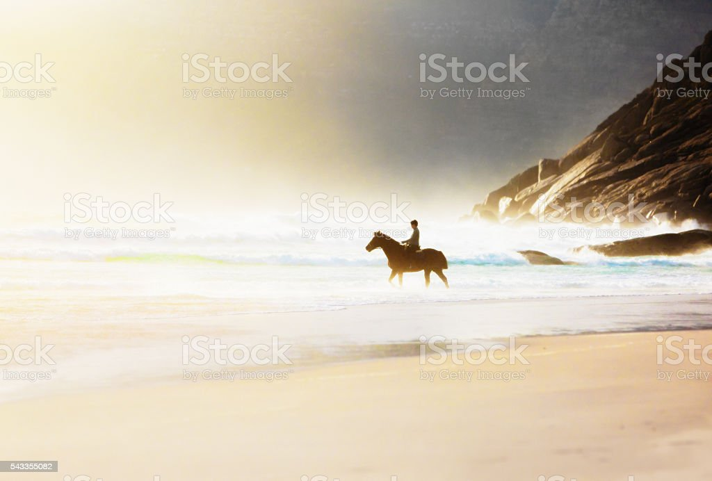 Horseback rider on beautiful deserted beach in misty pastel colors stock photo
