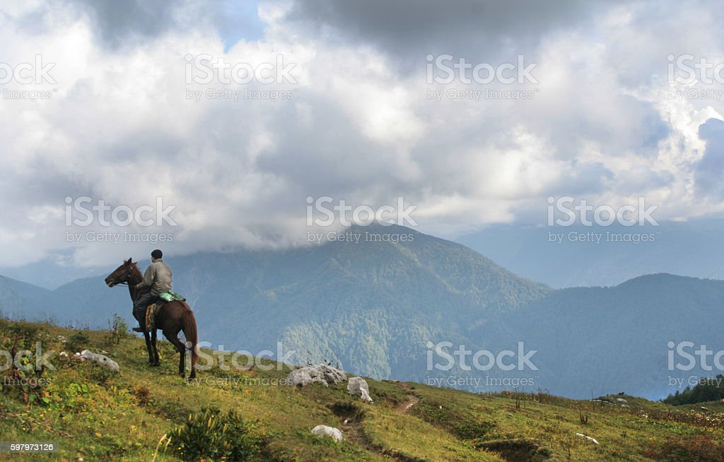 Horseman stay on peak of mountain and rest stock photo