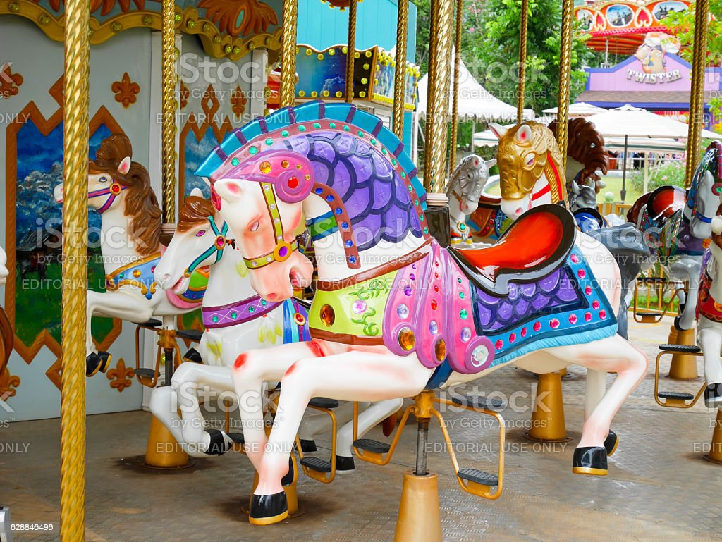 Horses on merry-go-round in amusement park stock photo