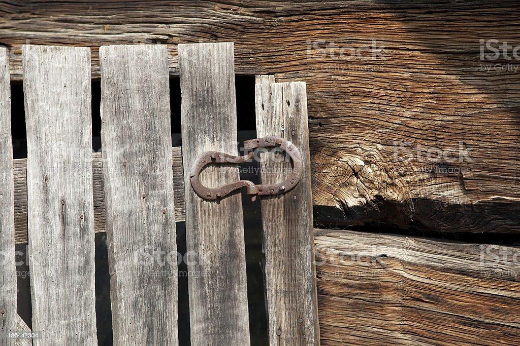 Horseshoe hinge on an old wooden door royalty-free stock photo