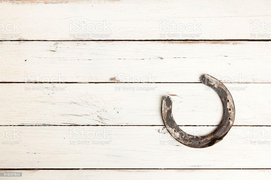 Horseshoe on white wooden background stock photo