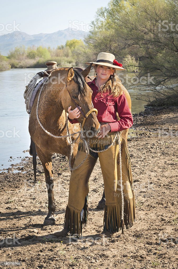 Horsewoman by river wearing hat royalty-free stock photo