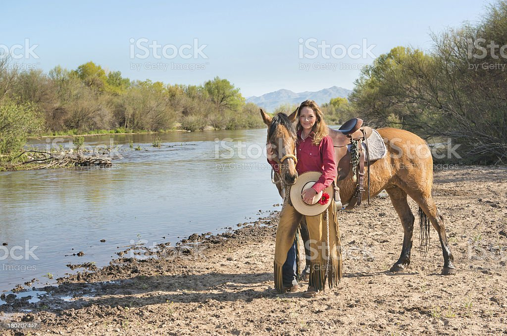 Horsewoman by river with horse royalty-free stock photo