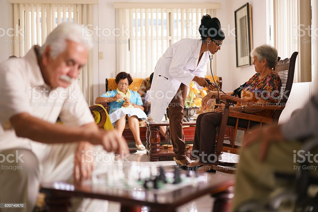 Hospice Doctor Measuring Blood Pressure To Senior Woman stock photo
