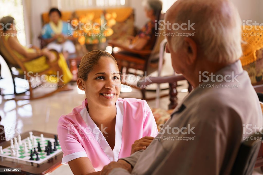 Hospice Nurse Helping Elderly Man On Wheelchair stock photo